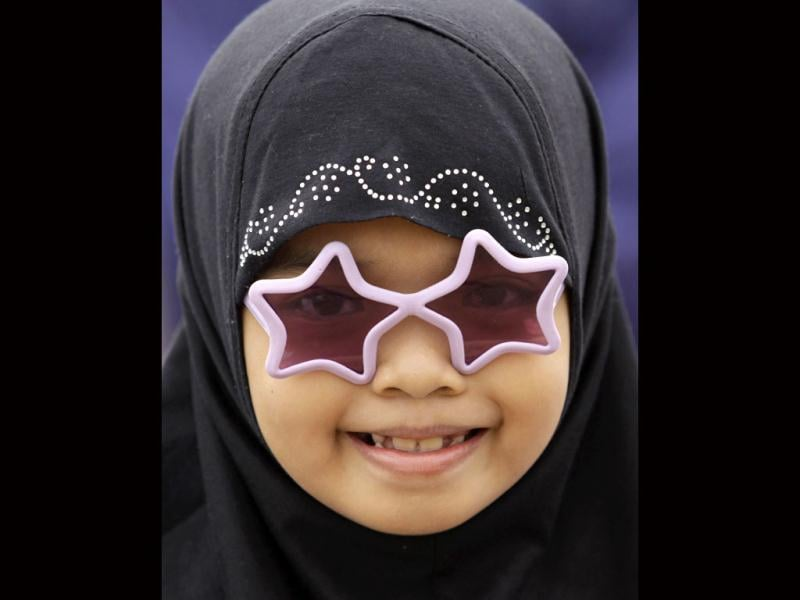 A Filipino Muslim girl wearing sunglasses smiles as they celebrate Eid-al Fitr at Manila's Rizal Park, Philippines (AP/Aaron Favila)