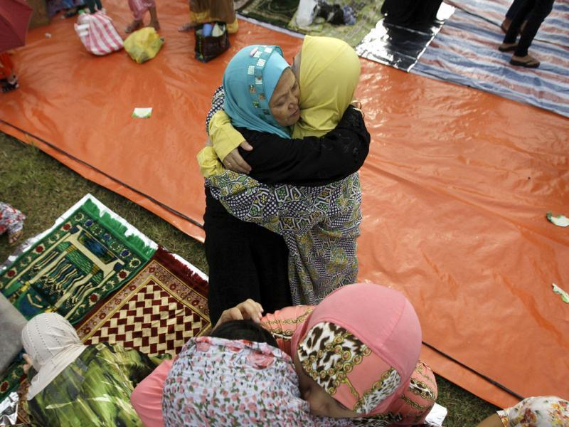 Philippine Muslim women embrace each other after prayers as they celebrate Eid-al Fitr at Manila's Rizal Park, Philippines.(AP Photo/Aaron Favila)