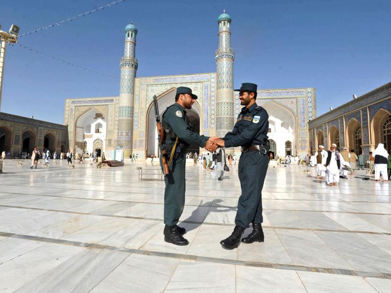 Afghan policemen shake hands after Eid ul-Fitr prayers at Jame mosque in Herat. (AFP/Aref Karimi)