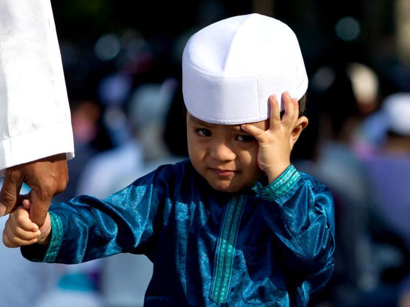 A Malaysian Muslim boy walks with his father after Eid ul-Fitr prayers at a mosque in Kuala Lumpur. (AFP/Mohd Rasfan)