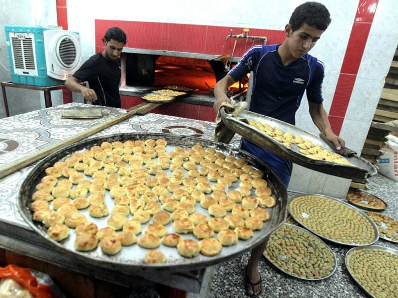 Iraqi men bake cakes and sweets for the occasion of Eid ul-Fitr in Baghdad's Sadr City neighborhood. (AFP/Ahmad Al-Rubaye)