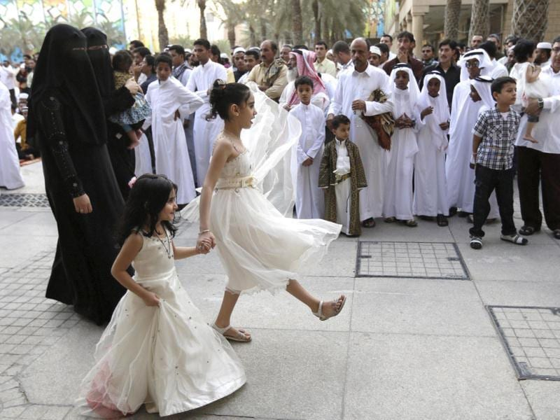 Families arrive to the Imam Turki bin Abdullah mosque to offer Eid ul-Fitr morning prayers to mark the end of the holy fasting month of Ramadan in Riyadh. (AP/Hassan Ammar)