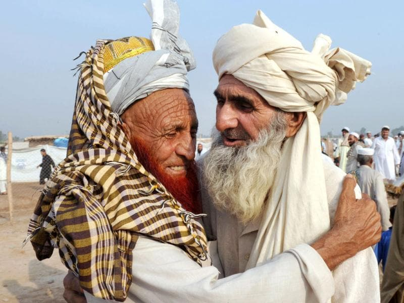 Pakistani internally displaced tribesmen, fleeing from military operations against Taliban militants in the Pakistani tribal region, hug after offering Eid ul-Fitr prayers at Jalozai, Pakistan's largest refugee camp. (AFP/ A. Majeed)
