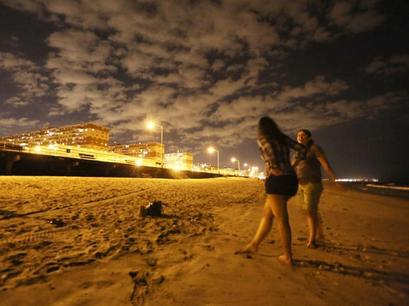 People gather at Rockaway Beach after dark in the Queens borough of New York City. Mario Tama/Getty Images/AFP
