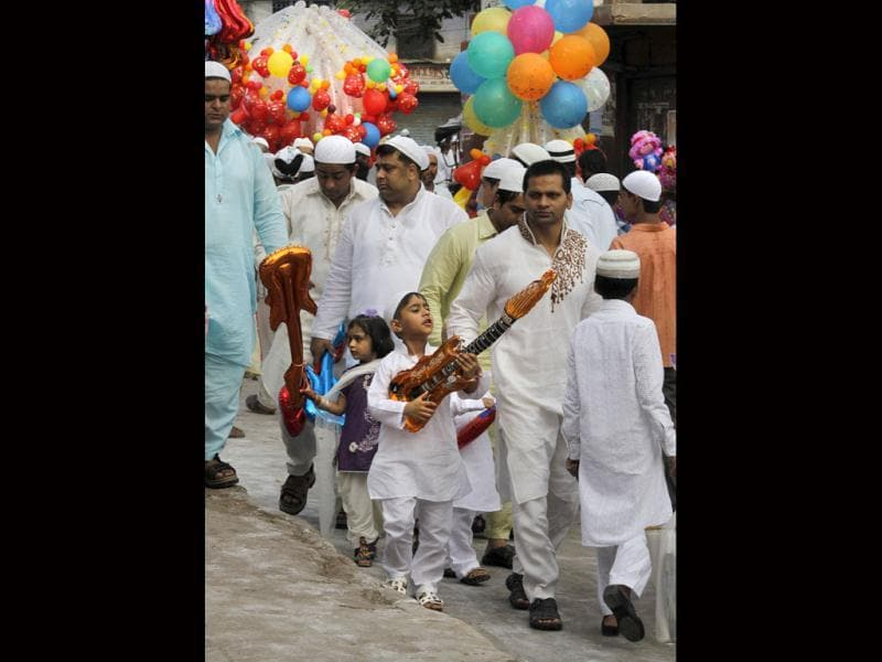 Children play with guitar-shaped balloons as they walk with their parents after offering Eid al-Ftr prayer at the Jama Masjid in New Delhi. (AP Photo/ Manish Swarup)