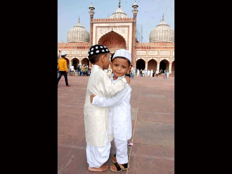 Children greet each other after offering their Eid-ul-Fitr prayers at Jama Masjid, in New Delhi . UNI Photo