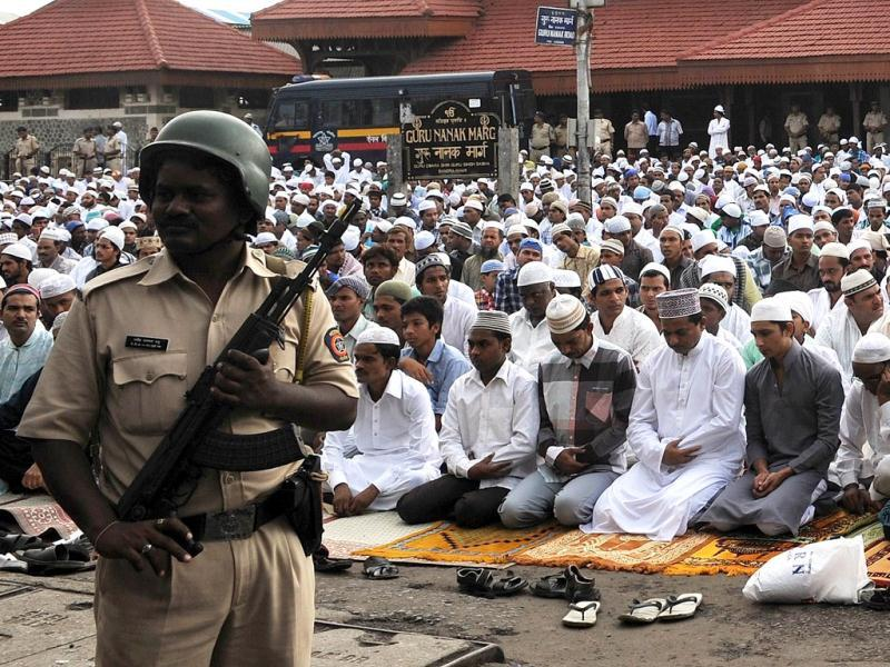 A police official stands guards as Muslims offer Eid al-Fitr prayers on a street outside the railway station in Mumbai . AFP Photo/ Punit Paranjpe