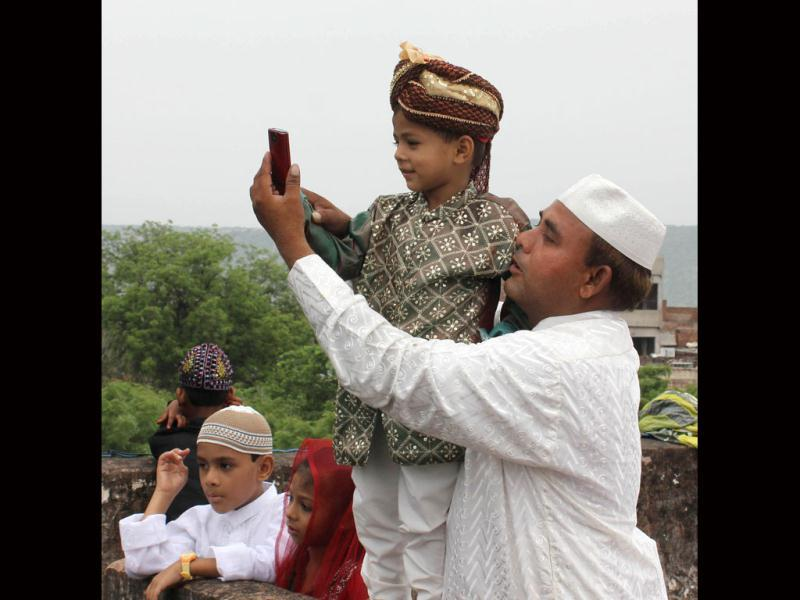 A kid clicks pictures during Eid-ul-Fitr prayers at Idgah mosque in Jaipur. UNI Photo
