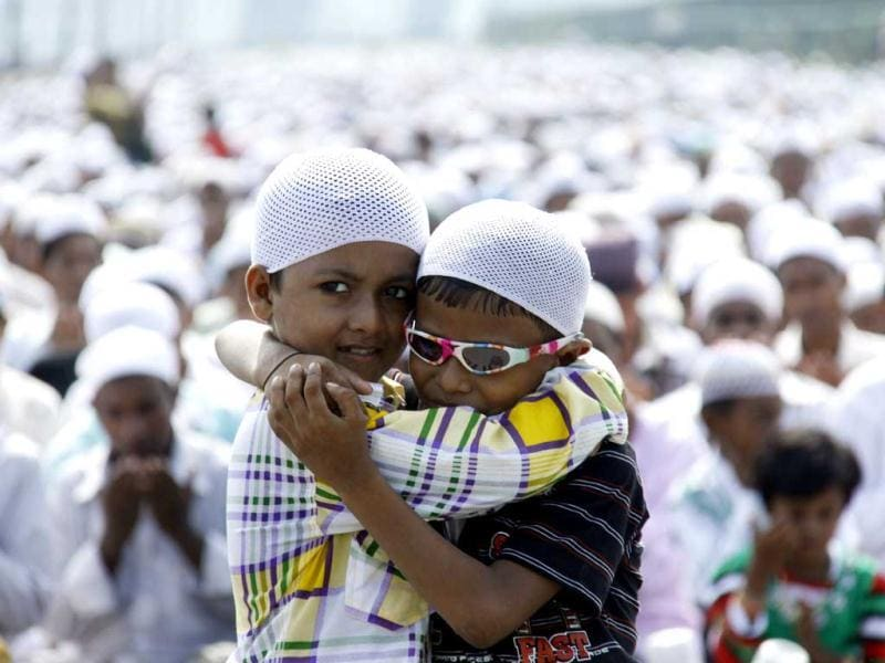 Two Muslim boys hug each other while devotees offer Namaz on the occasion of Eid-ul-fitr, in Gurgaon. Photo by Manoj Kumar/Hindustan Times