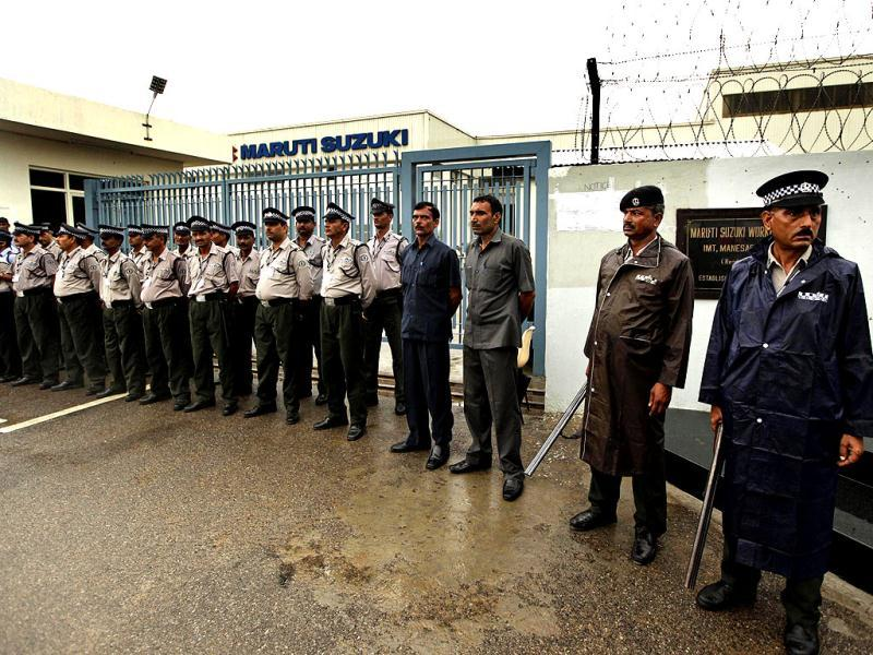 Security personnel stand outside the Maruti Suzuki factory at Manesar. AP Photo