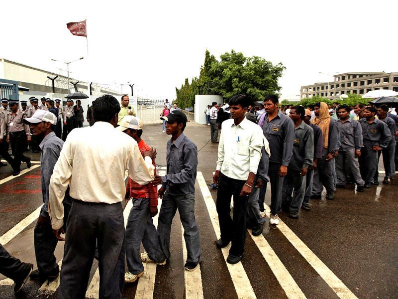Contract laborers stand in a queue outside the Maruti Suzuki factory at Manesar. AP Photo