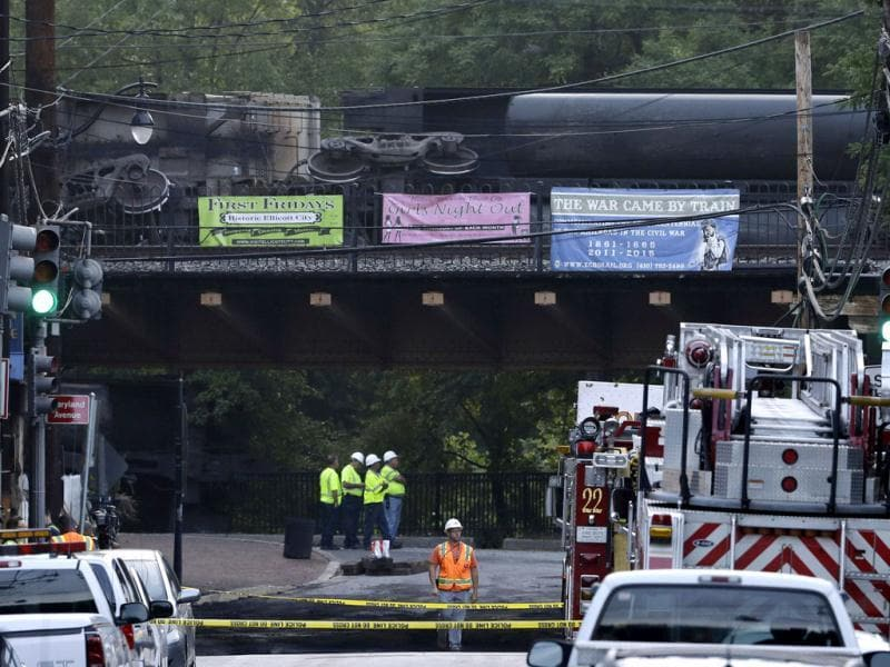 Officials stand underneath a bridge where part of a CSX freight train derailed overnight in Ellicott City, Md. (AP Photo/Patrick Semansky)