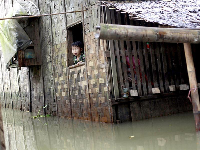 A flood-affected child looking out from a partially-submerged house at a village outside Pathein, in the Irrawaddy delta region of Myanmar. AFP Photo