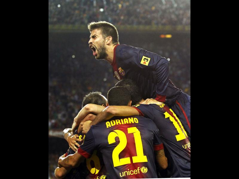 FC Barcelona's Gerard Pique, top, celebrates Andres Iniesta's, goal with team mates during a Spanish Supercup first leg soccer match against Real Madrid at the Camp Nou stadium in Barcelona, Spain. (AP Photo)