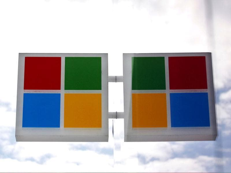 The new Microsoft logo is seen reflected in windows at a company store in Seattle. AP/Elaine Thompson