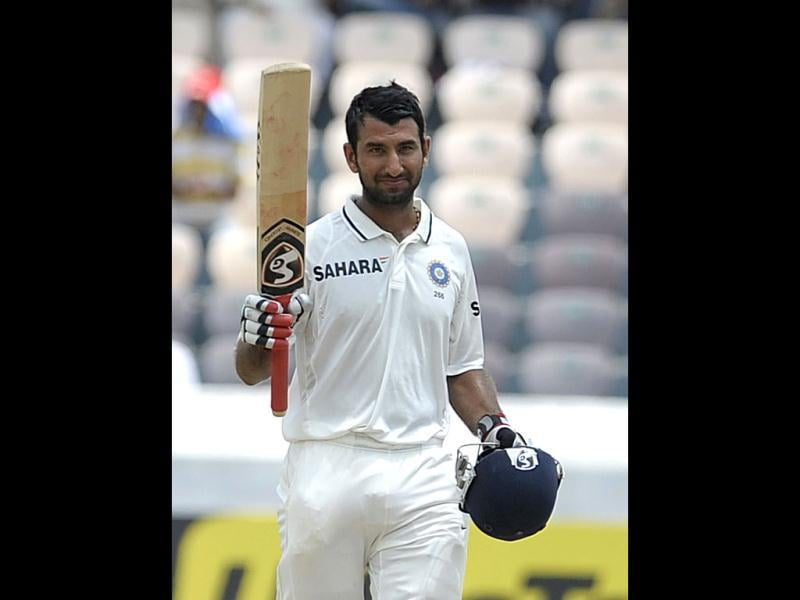 Cheteshwar Pujara raises his bat after scoring 150 runs during the second day of the first Test match between India and New Zealand at the Rajiv Gandhi International cricket stadium in Hyderabad. AFP/Noah Seelam