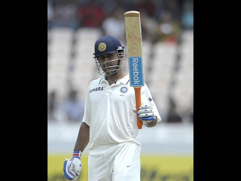 Mahendra Singh Dhoni raises his bat after scoring a half century during the second day of the first Test match between India and New Zealand at the Rajiv Gandhi International cricket stadium in Hyderabad. AFP/Noah Seelam