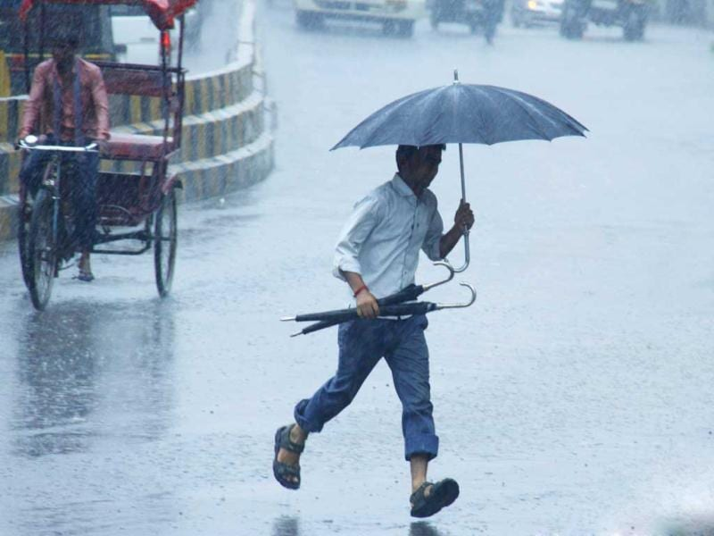 A pedestrian walks with an umbrella as it rains in Gurgaon. The monsoon rains were 2% below average in the week to August 22. HT Photo/Manoj Kumar