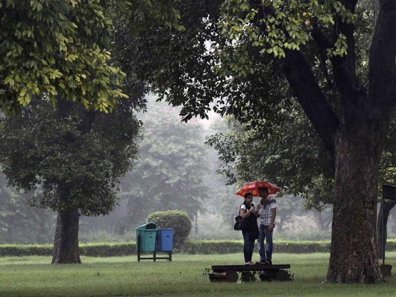 A couple stands under an umbrella on a platform in a park as it rains in New Delhi. Reuters/Adnan Abidi
