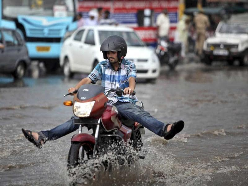 A man holds his legs up to prevent them from getting wet as he rides a motorbike through a waterlogged road after monsoon showers in Jammu. AP Photo/Channi Anand