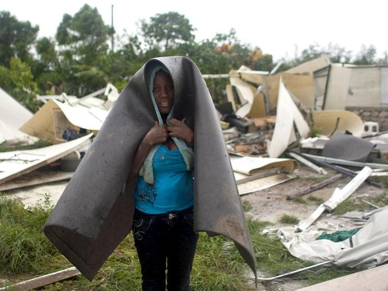 A woman covers herself with what's left of her home in a camp set up for people displaced by the 2010 earthquake that was destroyed by Tropical Storm Isaac in Port-au-Prince, Haiti. (AP Photo/Dieu Nalio Chery)
