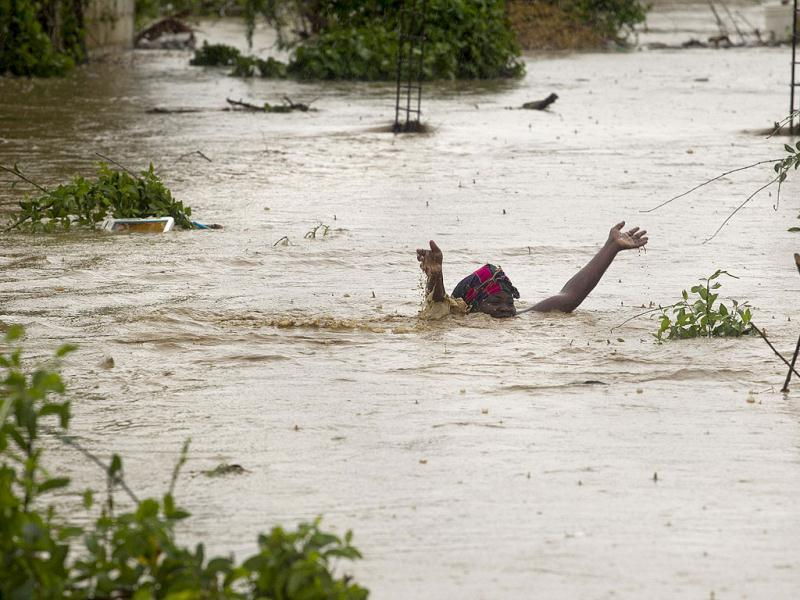 A woman wades through flood waters as she works to save her possessions from her flooded home in Port au Prince. Tropical Storm Isaac emerged over warm Caribbean waters slightly weaker but ready to regroup after dumping torrential rains on Haiti. Reuters/UN/MINUSTAH/Logan Abassi/Handout