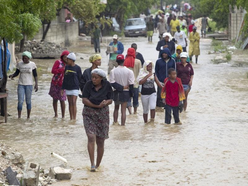 Residents of a low lying area in Port au Prince flee their flooded homes with their possessions. Tropical Storm Isaac emerged over warm Caribbean waters slightly weaker but ready to regroup after dumping torrential rains on Haiti. Reuters/UN/MINUSTAH/Logan Abassi/Handout
