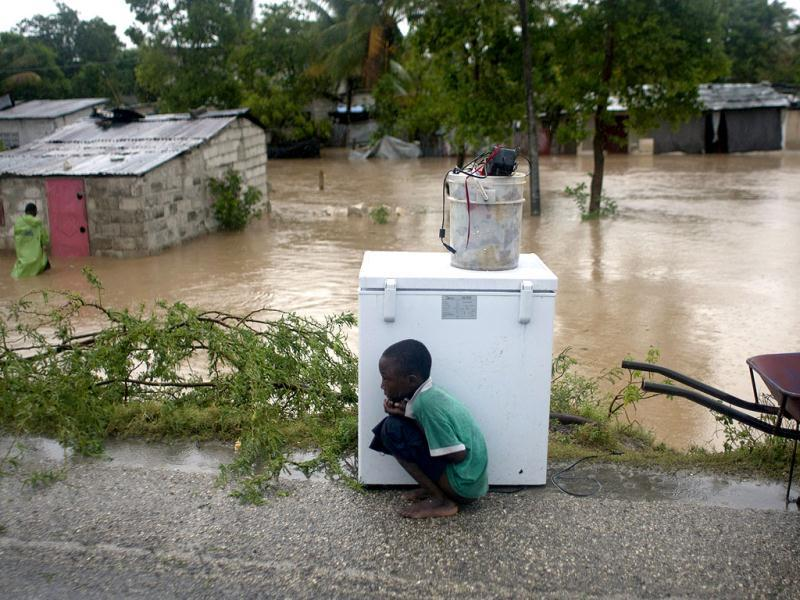 A boy tries to take cover from the cold behind an appliance sitting higher than the floodwaters triggered by Tropical Storm Isaac in Port-au-Prince, Haiti. (AP Photo/Dieu Nalio Chery)