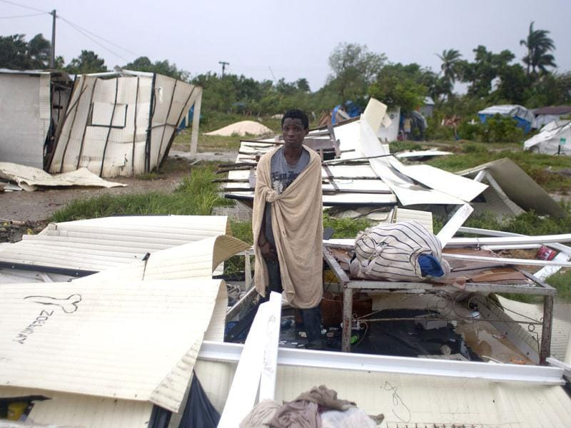 A man stands next to his bed after Tropical Storm Isaac destroyed his home and others at a camp set up for people displaced by the 2010 earthquake in Port-au-Prince, Haiti.(AP Photo/Dieu Nalio Chery)