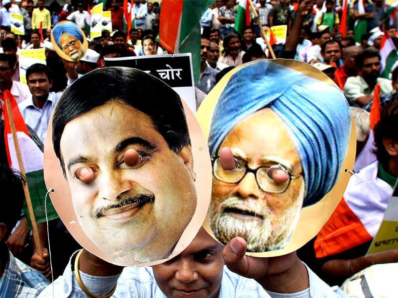 An India Against Corruption (IAC) activist shows posters of Prime Mininster Manmohan Singh and BJP President Nitin Gadkari during a protest on coal block allocation issue in New Delhi. PTI Photo/Manvender Vashist