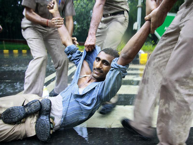 Police detain an activist of India Against Corruption (IAC) during a protest on coal block allocation issue in New Delhi. HT Photo/M Zhazo