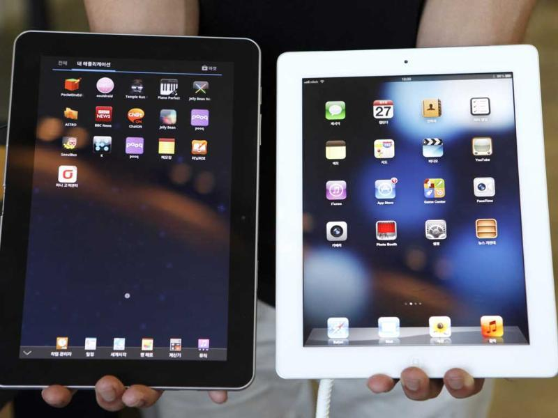 An employee holds up a Samsung Electronics' Galaxy Tab tablet computer (L) and an Apple iPad as he poses at a store in Seoul. (Reuters/Lee Jae-Won)
