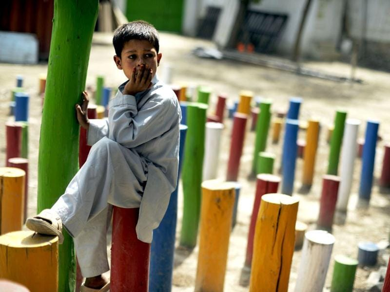 A boy rests as his friends rehearse before the 7th Afghanistan Juggling Championships in Kabul. AFP Photo/Jose Cabezas