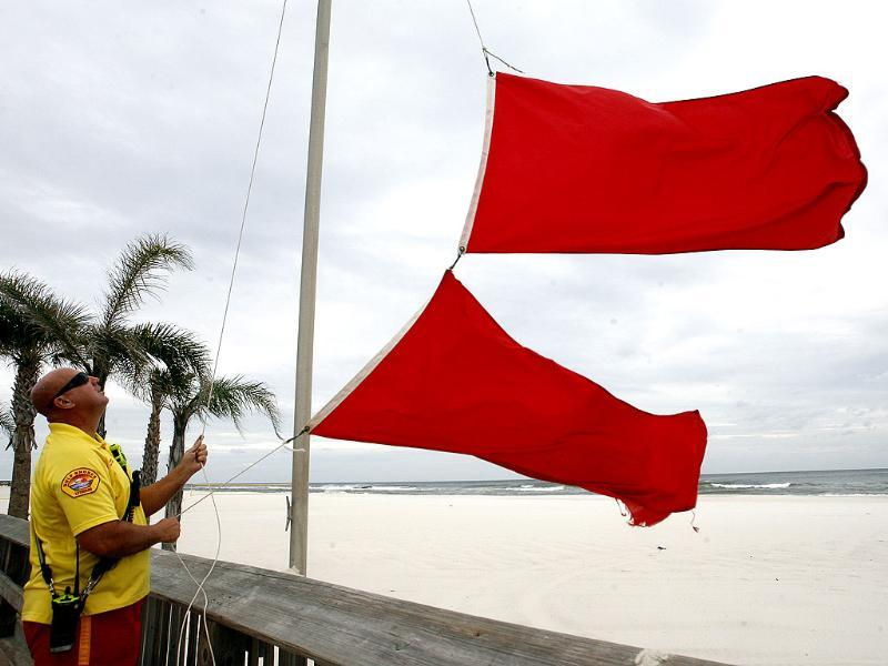Scott Smothers, a lifeguard with the Gulf Shores Beach Patrol changes the warning flag to double red flags closing the waters at the Gulf Shores Public Beach as Tropical Storm Isaac approaches the Gulf Coast, Alabama. AP/John David Mercer