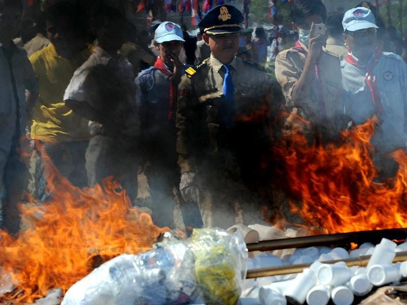 A Cambodian police looks at the flame and smoke from burning drugs during a destruction ceremony in Phnom Penh. Cambodian authorities burned more than one ton of drugs. AFP/Tang Chhin Sothy