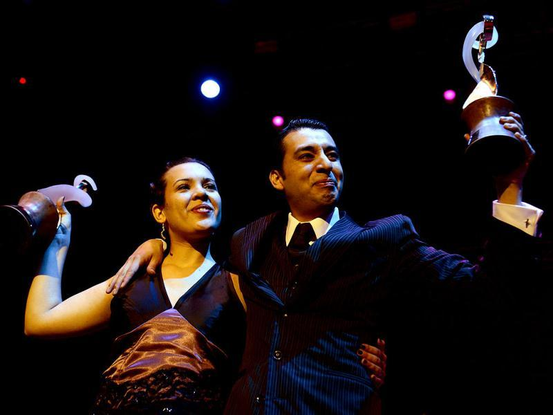 Argentina's Facundo Gomez Cross and Paola Palavecino Florence Sanz hold their trophies after winning the Tango Salon category at the Tango World Championship in Buenos Aires. AFP PHOTO / DANIEL GARCIA