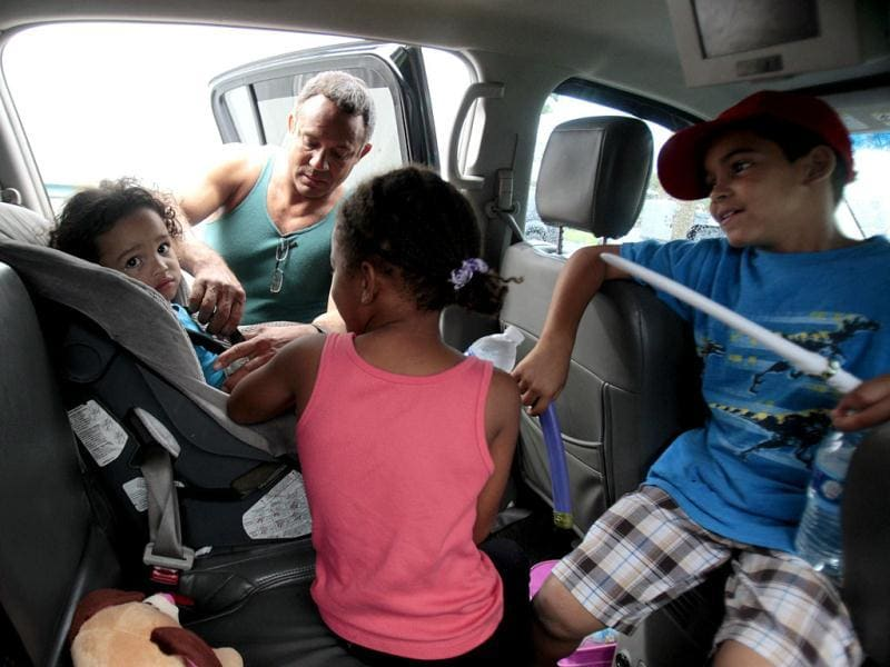 Jaden Fabian (L), is strapped into her car seat by Estanislao Fabian as her family evacuates their home as hurricane Isaac heads towards the Louisiana coast line in Oakville, Louisiana. Reuters Photo