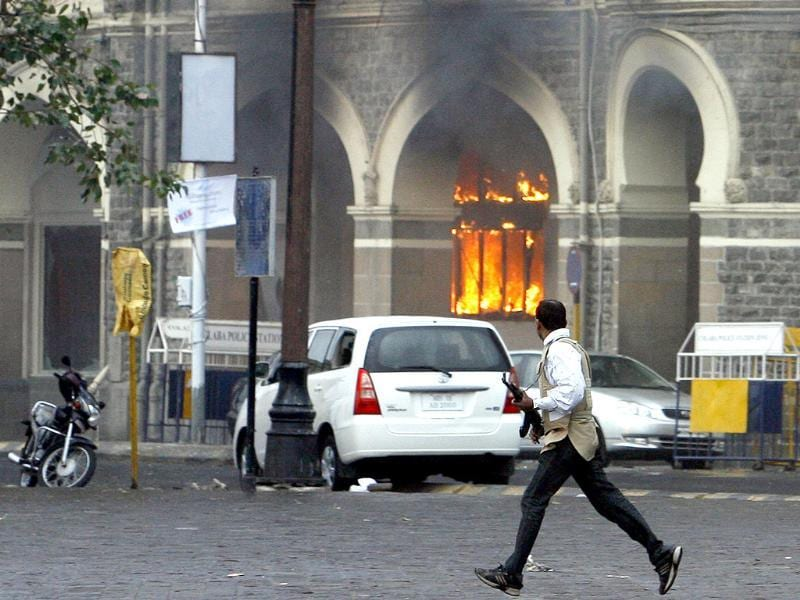 A member of the anti-terrorist squad runs in front of the burning Taj Mahal hotel during a gun battle in Mumbai on November 29, 2008. Reuters/Arko Datta