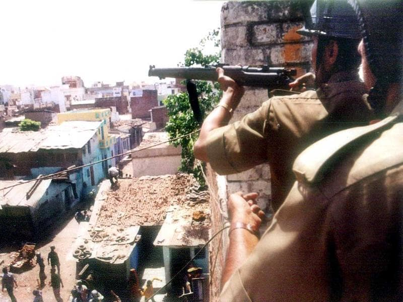 In this April 22, 2002 photo, a policeman takes aim with his rifle from the roof of a building as a mob riots down in the streets below in Ahmedabad. AFP photo