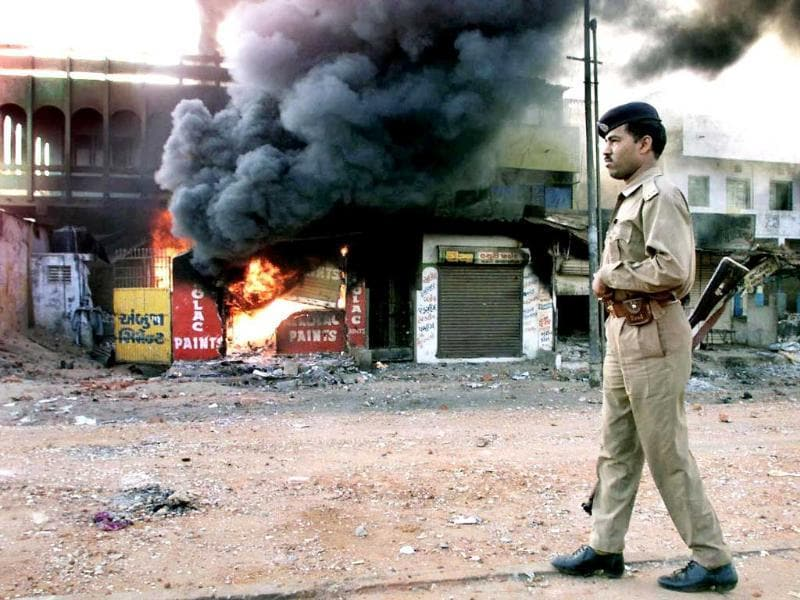 In this March 1, 2002 picture, a policeman looks on as a row of shops burn in Ahmedabad. A special court convicted a former BJP minister and 31 others over the Naroda Patiya massacre. AFP photo
