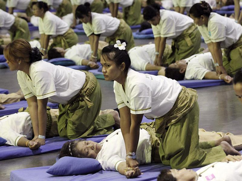 Thai masseuses perform mass massaging at a sports arena on the outskirts of Bangkok, Thailand. (AP Photo/Apichart Weerawong)