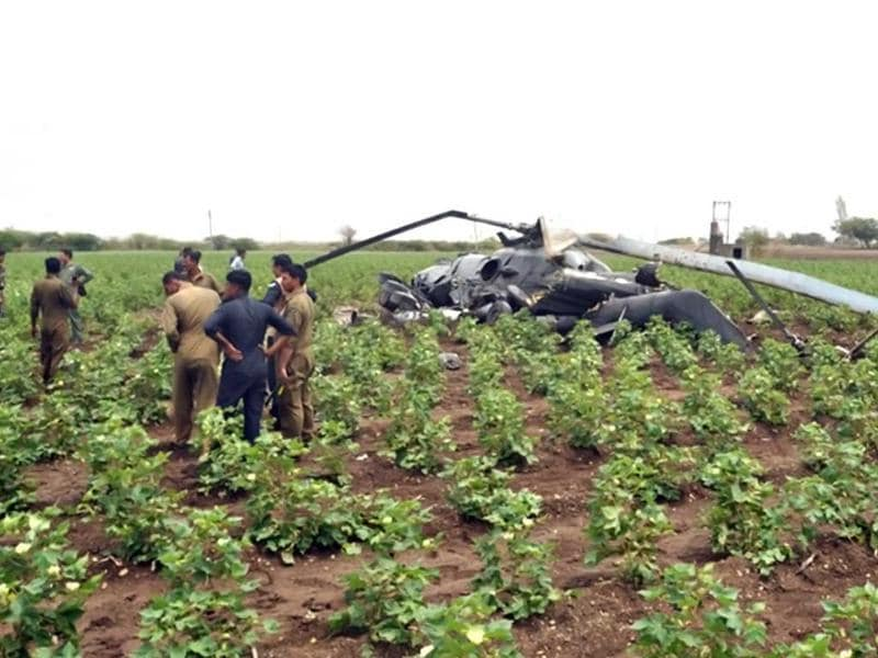 Air Force officials and rescue personnel stand near the wreckage of one of two crashed Indian Air Force Mi-17 helicopters following a mid-air collision near Jamnagar, some 330 kms from Ahmedabad. AFP photo