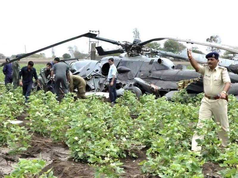 A police officer gestures as Indian Air Force (IAF) personnel inspect the wreckage after two air force helicopters collided and crashed at a field in Sarmat village, near Jamnagar in Gujarat. AP photo