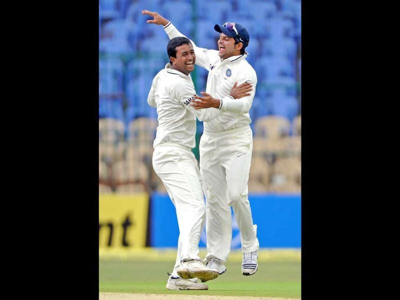 Pragyan Ojha (L) celebrates with teammate Suresh Raina the dismissal of New Zealand batsman Martin Guptill for 53 runs during the first day of their second Test match. AFP/Manjunath Kiran