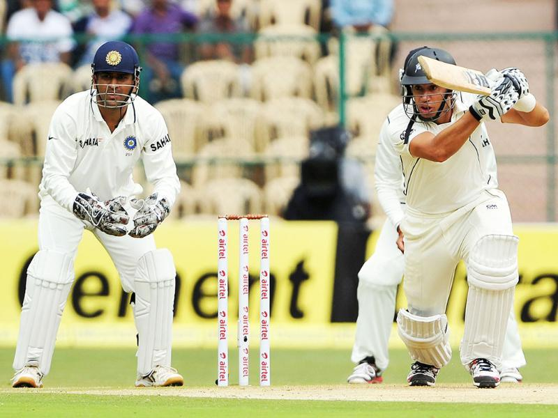 New Zealand batsman Ross Taylor (R) strikes a boundary as Mahendra Singh Dhoni looks on during the first day of their second Test match in Bangalore. AFP/Manjunath Kiran