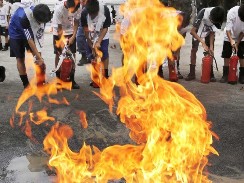 Junior high school students learn how to use fire extinguishers during a disaster drill in Tokyo to mark the Great Kanto Earthquake that hit the Tokyo metropolitan area in 1923. AP Photo/Itsuo Inouye