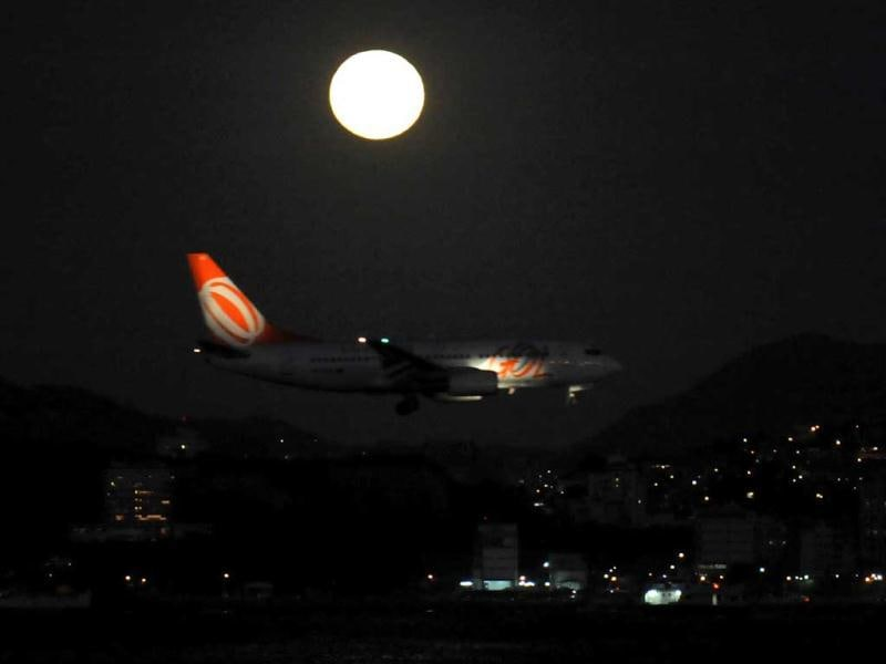 An airplane prepares to land at Santos Dumont domestic airport in Rio de Janeiro as a full moon shines in the night sky. AFP Photo/Vanderlei Almeida