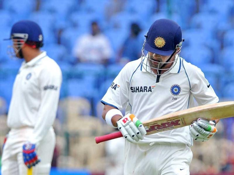 Gautam Gambhir walks back dejected to the pavilion after being bowled out for two runs while his teammate Virender Sehwag looks away during the 2nd day of the second Test match between India and New Zealand at the M Chinnaswamy Stadium in Bangalore. AFP Photo/Manjunath Kiran