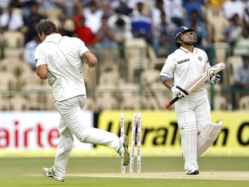 New Zealand bowler Doug Bracewell, left, runs to celebrate after taking the wicket of Sachin Tendulkar, right, during the second day of their second test match in Bangalore. AP Photo/Aijaz Rahi