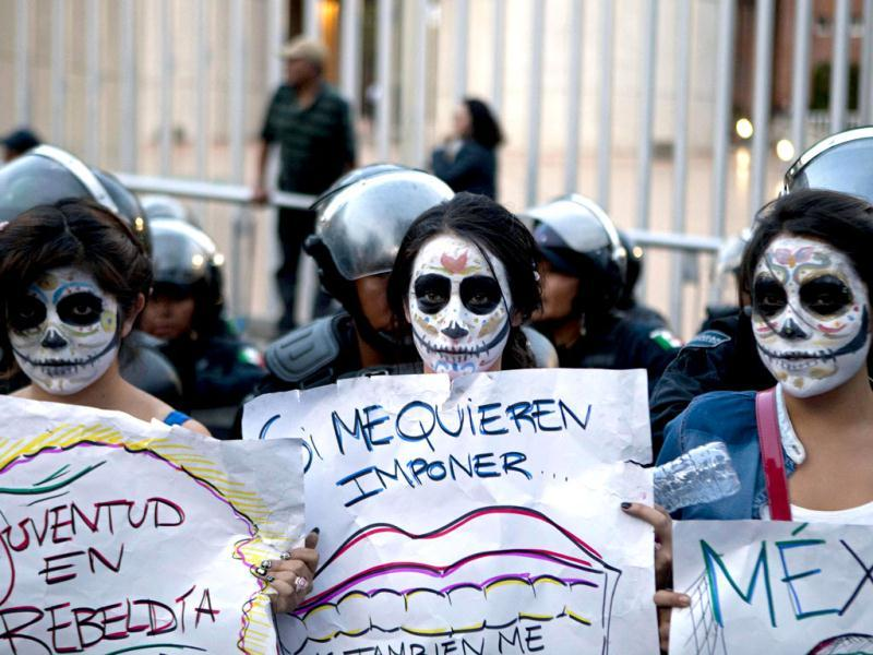 Youths protest the official presidential election results outside of the Federal Electoral Tribunal in Mexico City. Their signs read in Spanish